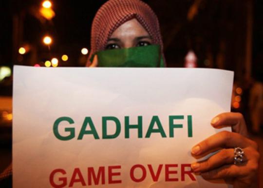 Imagen de una mujere libia con un cartel que dice 'Gadafi Game Over'